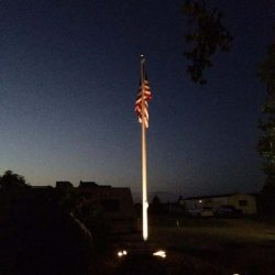 A light shining up at a flag pole at night - ND Flag Pole Guy
