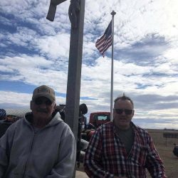 Two guys with cross and American flag in the back ground - ND Flag Pole Guy