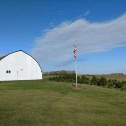 A large field with a flag pole installed - ND Flag Pole Guy