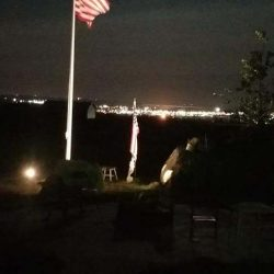 A flag pole lit up at night - ND Flag Pole Guy
