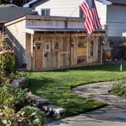 Shed in a back yard with American flag flying from roof - ND Flag Pole Guy