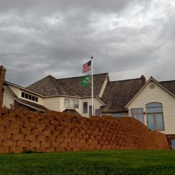 A commercial flag pole installed in front of a house with stone wall - ND Flag Pole Guy