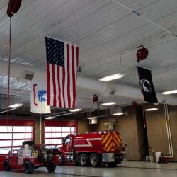 Inside of a firehouse with flags hanging from the ceiling - ND Flag Pole Guy