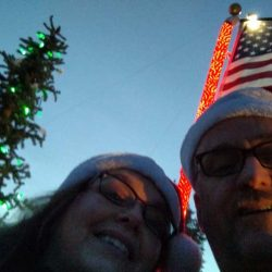 Couple taking a selfie with American flag and Christmas tree - ND Flag Pole Guy