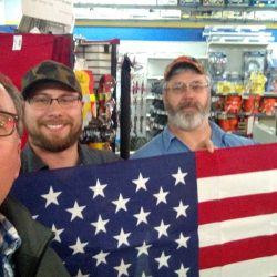 Three men holding up an American flag - ND Flag Pole Guy