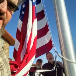 Three guys standing next to an installed flag pole - ND Flag Pole Guy