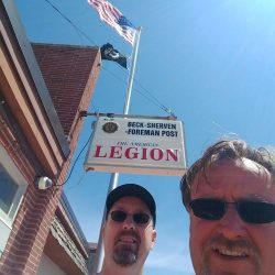 Two guys with commercial flag pole in front of The American Legion - ND Flag Pole Guy
