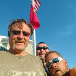Three happy guys in front of an installed flag pole - ND Flag Pole Guy