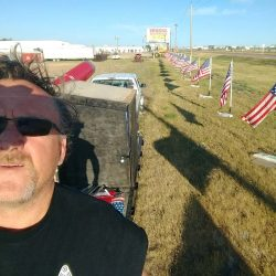 Flag pole installer with row of American flags - ND Flag Pole Guy