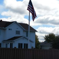 American flag installed in a yard behind a fence - ND Flag Pole Guy