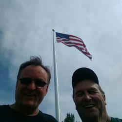 Two guys taking a picture with flag pole in the background - ND Flag Pole Guy