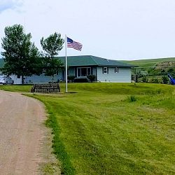 Farm house with American flag flying next to the road - ND Flag Pole Guy