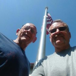 Two guys with flag pole above them - ND Flag Pole Guy