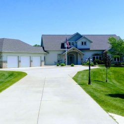 Large home with flag pole installed in the driveway - ND Flag Pole Guy