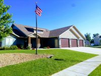 House with green lawn and American flag pole - ND Flag Pole Guy