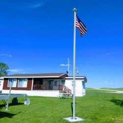 American flag flying on a sunny day in front of a house - ND Flag Pole Guy