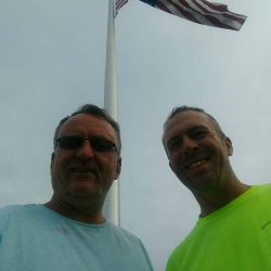 Two guys with an American flag flying above them - ND Flag Pole Guy