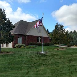 Large lawn in front of a house with an American flag pole - ND Flag Pole Guy