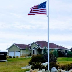 Rocks and landscaping surrounding a flag pole in front yard - ND Flag Pole Guy