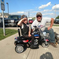 A man with a ND Flag Pole Guy shirt and daughter on a play motorcycle