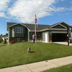 A family and dog in front of their house featuring a flag pole - ND Flag Pole Guy