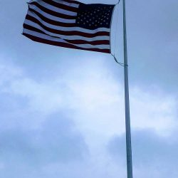 American flag flying in the wind with cloudy sky - ND Flag Pole Guy