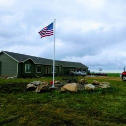 House with landscaping featuring a flag pole - ND Flag Pole Guy