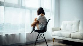 woman sitting on a chair looking out a window