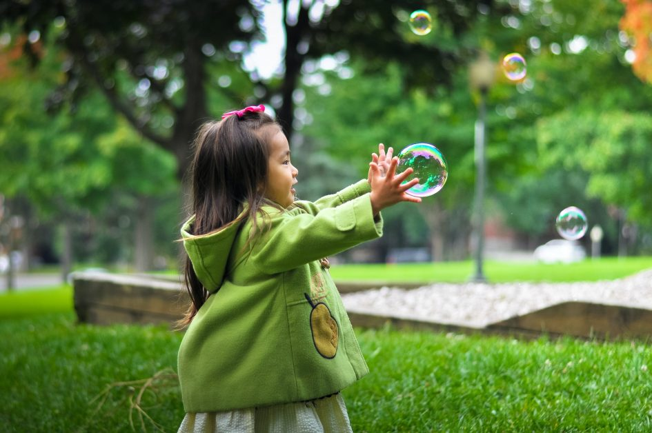 An image of young child playing with bubbles.