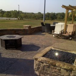 Patio with stone fireplace and seating area - New Horizon Landscaping