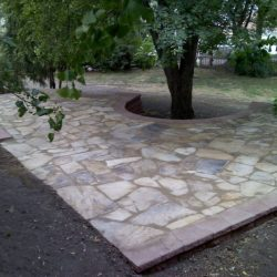 Stone patio with curved cutout for tree - New Horizon Landscaping