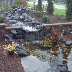 Rock water feature with waterfall and retaining wall - New Horizon Landscaping
