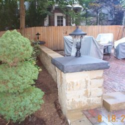 Stone patio with wall and endpost - New Horizon Landscaping