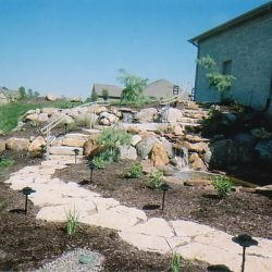 Slopped hill with retaining walls, landings, and water feature - New Horizon Landscaping