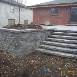 A stone retaining wall with steps - New Horizon Landscaping