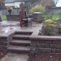 A patio and landscaping with retaining wall - New Horizon Landscaping