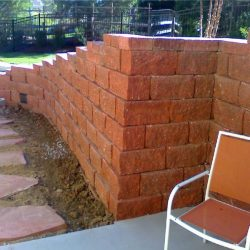vA red stone retaining wall with pavers - New Horizon Landscaping
