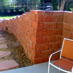 A red stone retaining wall with pavers - New Horizon Landscaping