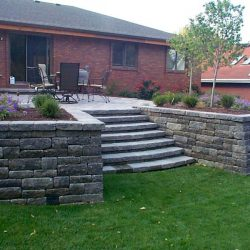 A patio with stone retaining wall and steps to lawn - New Horizon Landscaping