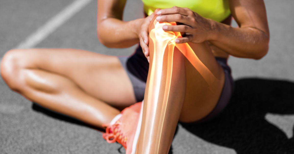 A woman holds her knee while the bones and joints are highlighted.
