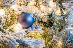 Image of an artificial tree with a silver ornament and fake snow.