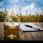 hot-tea-with-notebook-and-pen-on-wooden-table-in-flower-garden-100394655