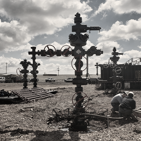 Image of two people kneeling near oil extraction equipment