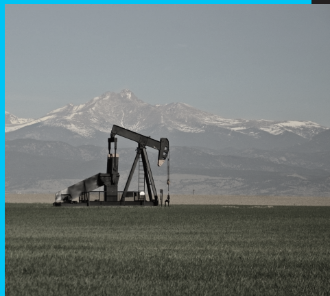 Image of an oil well in front of a mountain landscape