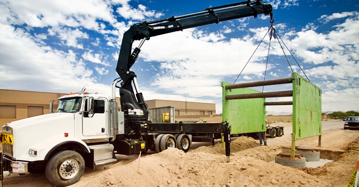 image of flatbed semi with crane, lowering a trench box into the ground