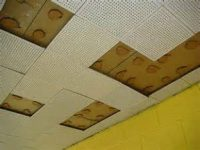 A ceiling covered in ventilated white ceiling tiles is missing several tiles which are being tested for asbestos.