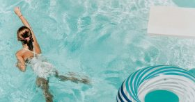 Girl swims in pool near diving board
