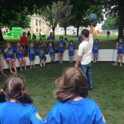 Explaining gaga ball rules to kids in a park.