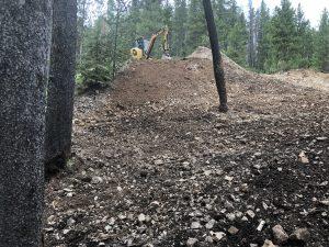 Mini excavator atop a pile of soil