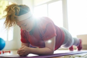 Portrait of young obese woman working out on yoga mat in fitness studio: holding plank